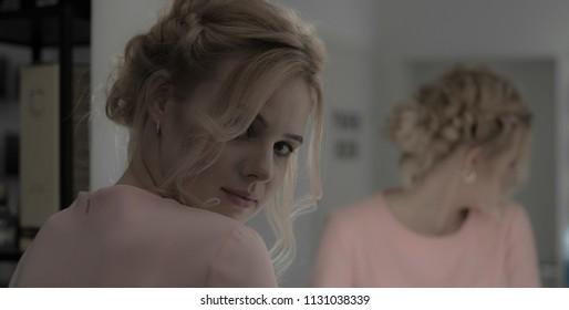 Young sensual girl with professional makeup look at camera reflected at mirror