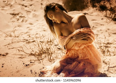 Young sensual lady with closed eyes sits in a desert in beautiful pink dress