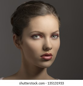 young sensual lady with purple make-up, perfect skin, brown hair looking in camera on gray background