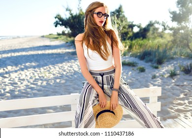 Young sensual pretty blonde woman posing at lonely beach, stylish modern hipster outfit and straw hat, luxury vacation mood.
