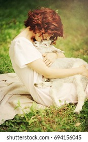 Young sensual red-haired woman hugging small goat. Animals are our friends concept. Love and protect animals