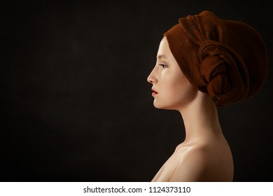 young sensual topless woman with closed eyes in turban on black background with copy space