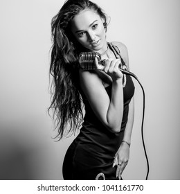 Young sensual woman in black dress with microphon. Black-white portrait.