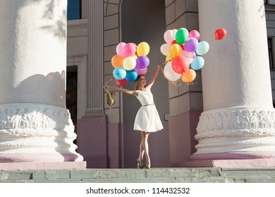 Young sensual woman with colorful latex balloons keeping her dress, urban scene, outdoors