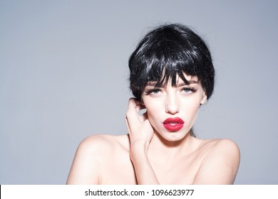 Young sensual woman with full red lips and winged eyeliner isolated on gray background. Sexy girl with perfect make-up posing topless, femme fatale, seduction concept.