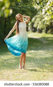 Young sensual woman in long white and blue dress outdoors poses. Professional style.