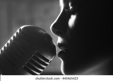 young sensual woman sexy silhouette profile with pretty face near studio silver microphone on wooden background, closeup
