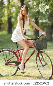 Young sensual woman in white with bicycle outdoors. Professional style.