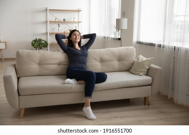 Young serene asian woman rest on soft stylish couch after finishing household chores enjoy tranquility feeling satisfied. Peaceful vietnamese lady chill at modern studio apartment breath fresh air nap