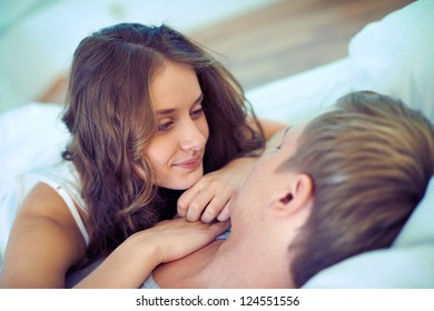 Young serene couple lying in bed