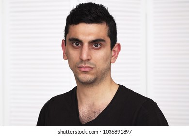 Young serious arabic man looking at camera, white background
