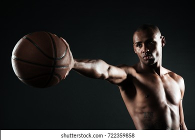 Young serious basketball player holding ball with one hand, looking away, over black background