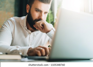 Young serious bearded businessman sitting in office at table and using laptop. Man works on computer, checks e-mail, chatting, blogging. Online marketing, education, social network, e-learning.