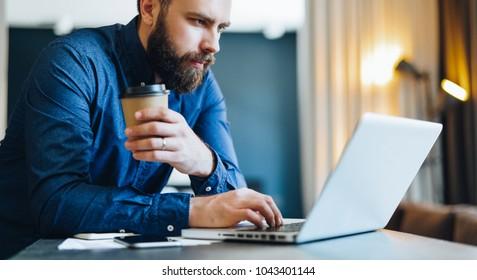 Jeune homme d'affaires sérieux et barbu travaillant sur ordinateur à table, buvant du café. L'homme analyse l'information, les données, élabore un plan d'affaires. Travailleur indépendant, entrepreneur.Marketing en ligne, éducation, e-learning.