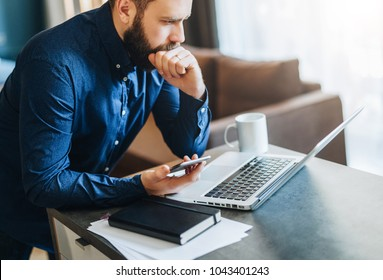 Young serious bearded businessman working on computer, holding smartphone, thinking. Man analyzes data, information, planning. Freelancer working at home.Online marketing, education, e-learning.