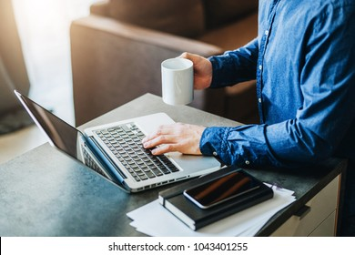 Young serious bearded businessman working on computer at table, drinking coffee. Man analyzes information, data, checking email. Freelancer working at home. Online marketing, education, e-learning.