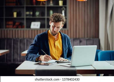 Young serious bearded Caucasian blogger dressed smart casual writing notes in agenda and looking at laptop while sitting in cafeteria.