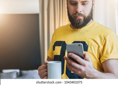 Young serious bearded man stands in room and using smartphone. Guy looking at screen of phone while drinking coffee. Man working at home. Social networks, online marketing, education, e-learning.
