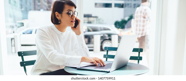 Young serious business woman in eyewear checking banking account on laptop while talking on cellular phone with service operator, female owner having mobile conversation while browsing information