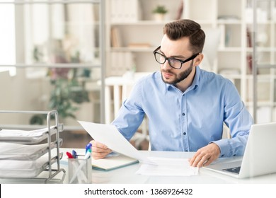 Young serious businessman in eyeglasses reading financial paper or contract while sitting by desk in office