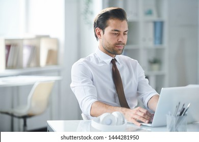 Young serious businessman looking at laptop display by his workplace