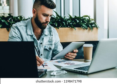 Young serious businessman is sitting in office in front of laptops, using digital tablet, making notes on chart. Freelancer analyzes data, develops development strategy. Business education for adults.
