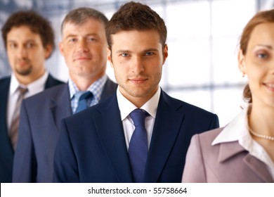 Young serious businessman standing in the row with his colleagues.