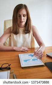 Young serious businesswoman sitting at the table and examining business diagrams on digital tablet at offcie