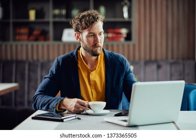 Young serious Caucasian businessman dressed smart casual drinking coffee in cafe and looking at laptop.