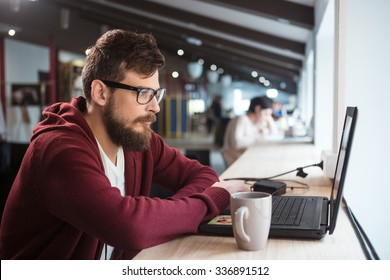 Young serious concentrated man in glasses sitting in office and using laptop