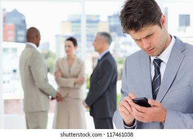 Young serious executive using his mobile phone to send a text