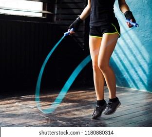 young serious female boxer in wrapped hands warming up, jumping on skipping rope in gym. Fit woman preparing to boxing competition. Wellness, fighting, motivation, self defense concept