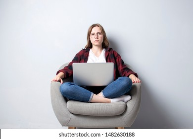 young serious girl with a laptop sitting on a soft comfortable chair and looking at the camera, a woman using a computer against a white blank wall, she freelancing and correcting glasses, copy space