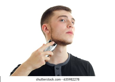 young serious guy raised his head and shaves his beard is isolated on a white background