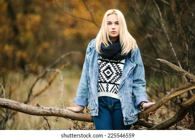 Young serious handsome blonde woman in jeans, scarf, and sweater, posing in autumn background