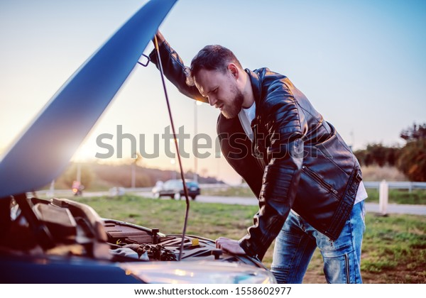 Young serious handsome caucasian bearded blond man in leather jacket looking engine of his car under the hood. Something went wrong.