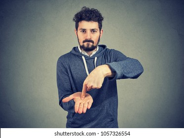 Young serious hipster man asking for more money to pay back debt