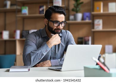 Young serious indian professional business man, focused ethnic male student wearing glasses working on laptop, remote studying using computer looking at screen watching seminar webinar at home office.