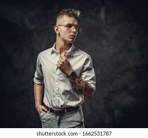 Young, serious looking, adult guy wearing a white shirt with tattoos on his hand posing in a dark studio, and staring on the side.
