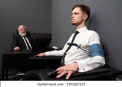 Young, serious man with beard sitting on black chair in grey room and checking with computer polygraph. Attached sensors for measuring and writing characteristics of body. Elderly man testing.