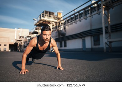 Young serious man doing pushups outdoor on industrial background. concentrated sportsman doing exercise outdoor