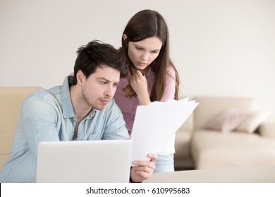 Young serious man holding papers, reading them attentively, sitting with laptop indoors. Anxious woman standing next to him looking at documents. Unpaid domestic bills, checking documentation