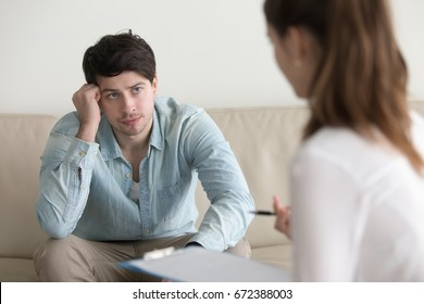Young serious man sitting on the couch listening attentively to advices of psychologist, doctor or psychotherapist, discussing medical test results, explaining diagnosis, treatment methods