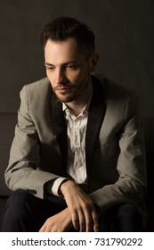 young serious man with an unshaven face in a suit with a pensive face on a dark background