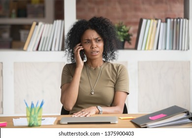 Young serious mixed race office worker female sitting at desk at workplace holding mobile phone makes business call listens client claims feels displeased annoyed and anxious, problems at work concept