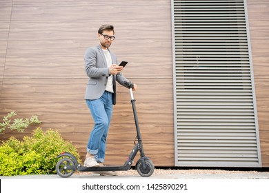 Young serious mobile employee in smart casual keeping one leg on scooter while texting in smartphone in urban environment