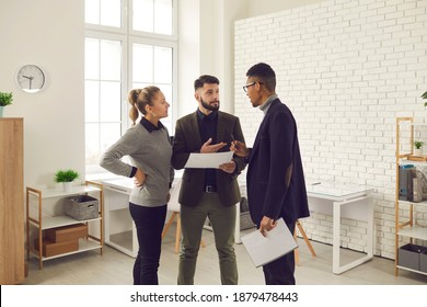 Young serious office workers of different nationalities discuss the project together in a bright office. One woman and two men are looking for ways to solve business problems. Concept of teamwork.