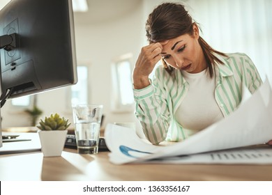 Young serious pensive businesswoman is working in the office. She is surprised about something she is looking on the paper document.