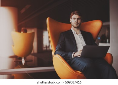 Young serious successful man entrepreneur in formal business suite with a beard sitting on orange armchair with laptop in luxury office interior, preparing to business meeting