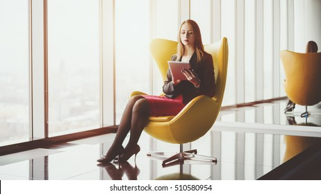 Young serious successful woman entrepreneur in a red dress and jacket sitting on yellow armchair, working on tablet, surfing internet in luxury office interior, preparing to business meeting